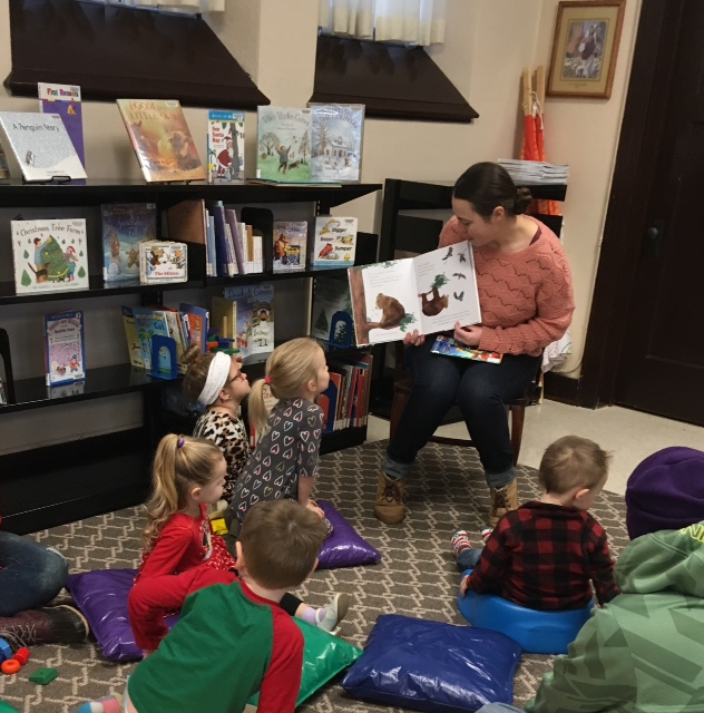 Librarian reads to a group of kids during Story Time