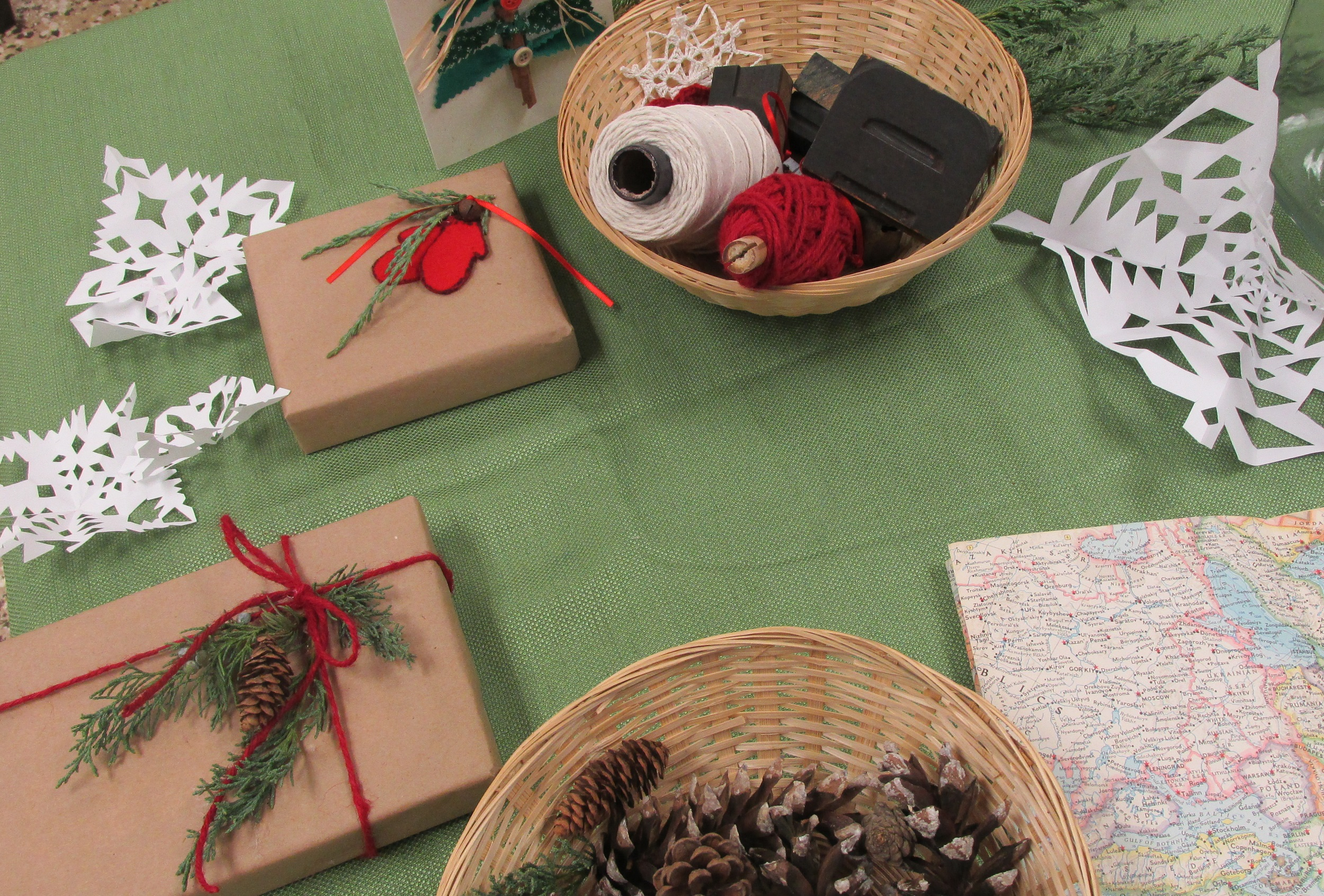 Table with wrapped presents, paper snowflakes, and pinecones